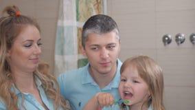 Moeder en vader die weinig dochter schone tanden onderwijzen stock videobeelden