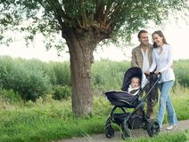Moeder en vader in openlucht en duwende baby die in kinderwagen lopen Stock Afbeeldingen