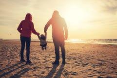 Moeder en vader slingerend kind door de wapens op het strand stock foto
