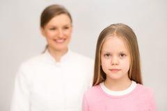 Moeder en verpleegster die weinig dochter onderzoeken. Isolat Royalty-vrije Stock Afbeelding