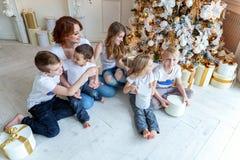Moeder en vijf kinderen dichtbij Kerstboom thuis royalty-vrije stock foto's