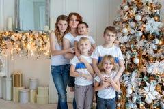 Moeder en vijf kinderen die Kerstboom thuis verfraaien stock afbeelding