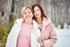 Moeder en volwassen dochter die in de winter bossneeuwval lopen stock afbeeldingen