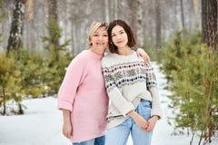 Moeder en volwassen dochter die in de winter bossneeuwval lopen royalty-vrije stock afbeeldingen