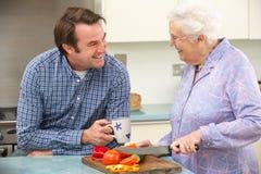Moeder en volwassen zoon die maaltijd samen voorbereiden Royalty-vrije Stock Fotografie