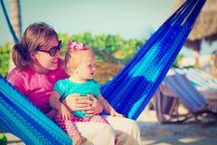 Moeder en weinig die dochter in hangmat wordt ontspannen Stock Foto