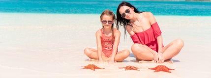 Moeder en weinig dochter die van tijd genieten bij tropisch strand royalty-vrije stock fotografie