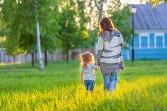 Moeder en weinig dochter die in zonnig park lopen Stock Foto's