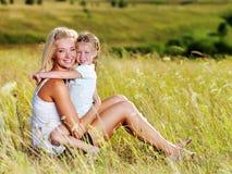 Moeder en weinig dochter op weide royalty-vrije stock afbeelding