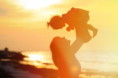 Moeder en weinig dochterspel bij zonsondergang Stock Afbeelding