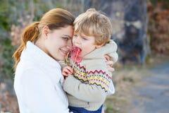 Moeder en weinig jong geitjejongen in park of bos, in openlucht stock foto's