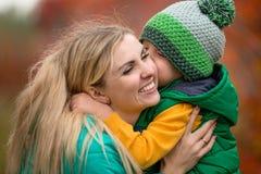 Moeder en weinig zoon die in de herfstpark lopen Het kind koestert en kust zacht mamma op de wang royalty-vrije stock foto