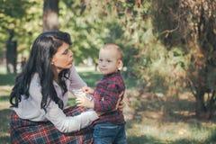 Moeder en weinig zoon die in een park spelen stock fotografie