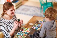 Moeder en weinig zoon die samen onderwijskaartspel voor c spelen Stock Fotografie