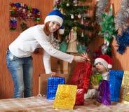 Moeder en weinig zoon met de giften van Kerstmis Stock Afbeeldingen