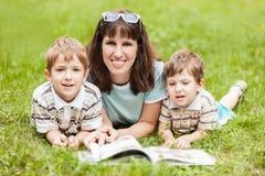 Moeder en zonen die boek lezen openlucht Stock Foto's