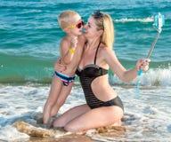 Moeder en zoon in badpakken en zonnebril die een selfie op een mobiele telefoon op de overzeese kust nemen royalty-vrije stock fotografie