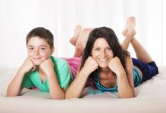 Moeder en zoon in bed stock foto's
