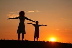 Moeder en zoon bij zich zonsondergang het uitrekken Stock Afbeeldingen