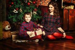 Moeder en zoon dichtbij een Kerstboom Stock Foto's