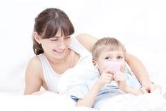 Moeder en zoon die aan muziek luisteren stock foto