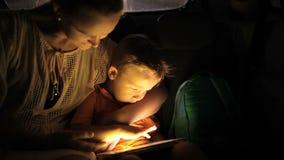 Moeder en zoon die aanrakingsstootkussen in auto gebruiken bij nacht stock footage