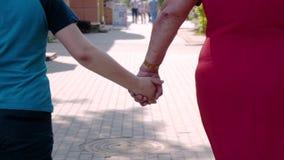 Moeder en zoon die de straten van de stad hand in hand lopen Emotioneel Ogenblik Close-up van hun handen stock video