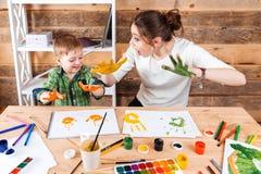 Moeder en zoon die drukken maken door geschilderde handen op papier royalty-vrije stock foto