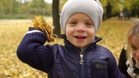 Moeder en zoon die gele bladeren in het Park werpen stock footage