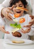 Moeder en zoon die hamburger maken Stock Afbeelding