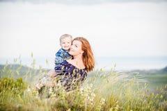 Moeder en zoon die in het gras koesteren Stock Afbeeldingen