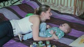 Moeder en zoon die kietelend gevoel kietelend gevoelstrijd in bed hebben stock video