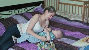Moeder en zoon die kietelend gevoel kietelend gevoelstrijd in bed hebben stock footage