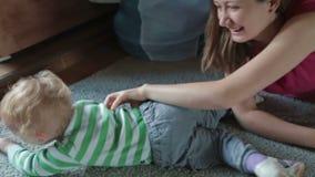Moeder en zoon die kietelend gevoel kietelend gevoelstrijd hebben stock videobeelden