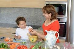 Moeder en zoon die lunch voorbereiden die eieren en glimlach gebruiken royalty-vrije stock fotografie