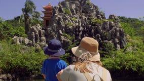 Moeder en zoon die macaqueapen bekijken die op rotsen springen Aapeiland, Vietnam stock footage