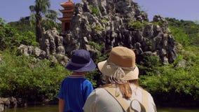 Moeder en zoon die macaqueapen bekijken die op rotsen springen Aapeiland, Vietnam stock video