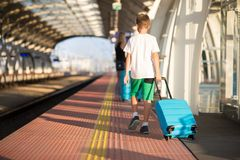Moeder en zoon die met blauwe bagagekoffer op stationplatform lopen royalty-vrije stock afbeelding