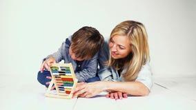 Moeder en zoon die met een rekenmachine leren te berekenen stock video