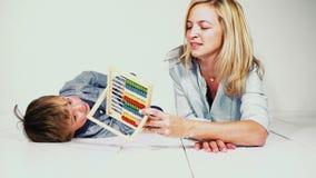 Moeder en zoon die met een rekenmachine leren te berekenen stock videobeelden