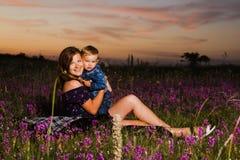 Moeder en zoon die op avondweide koesteren Stock Fotografie