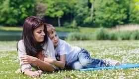 Moeder en zoon die op gras liggen stock foto's