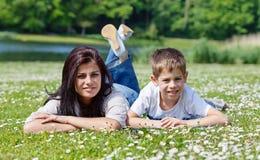Moeder en zoon die op gras liggen stock foto