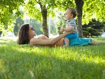 Moeder en zoon die op het gras liggen Stock Afbeelding
