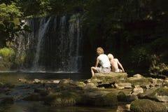 Moeder en zoon die van de waterval genieten royalty-vrije stock foto