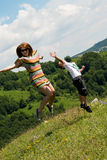 Moeder en zoon die in weide springen stock fotografie