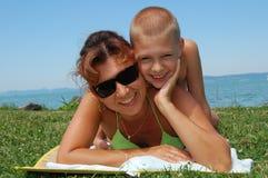 Moeder en zoon die in zon liggen Stock Afbeeldingen