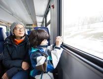 Moeder en zoon in een spoorwegvervoer stock fotografie
