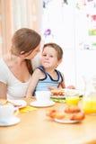 Moeder en zoon in keuken bij ochtend stock afbeeldingen