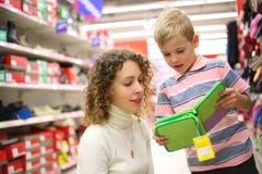 Moeder en zoon met doos in winkel royalty-vrije stock afbeeldingen